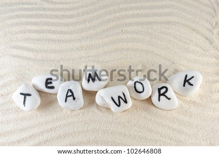 Teamwork word on group of stones with sand background