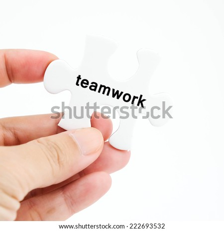 Teamwork word on white puzzle piece in hand isolated on white background, solution concept, business background
