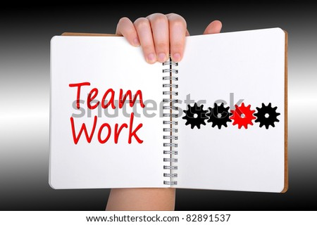 Teamwork words and gear on book