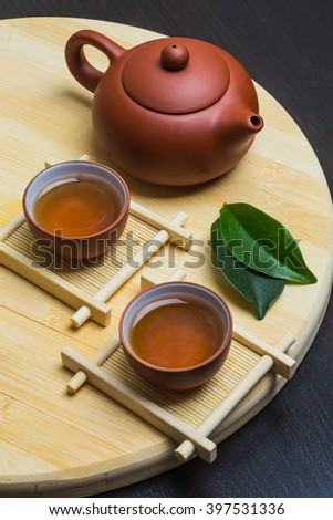Teapot and a cup of green tea on wooden table