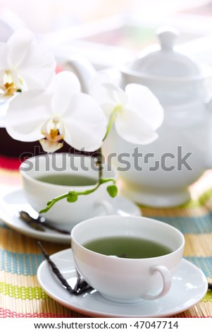 Teapot and a cup of green tea.Very challow depth of field to give dreamy effect. - stock photo