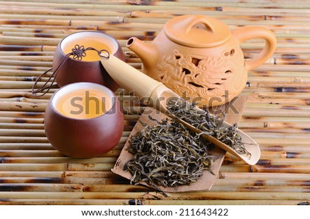 Teapot and aromatic oolong tea on bamboo mat background - stock photo
