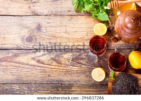 Teapot and cup of tea with mint and lemon on wooden table, top view - stock photo