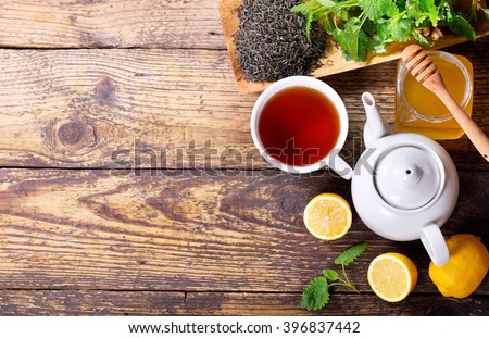 Teapot and cup of tea with mint and lemon on wooden table, top view