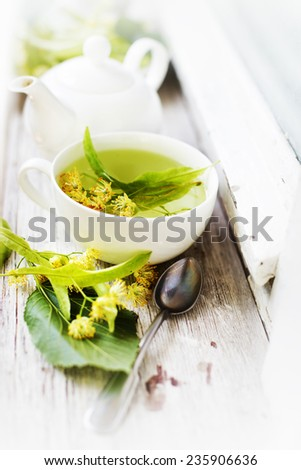 teapot and cup with linden tea and flowers on wooden table - stock photo