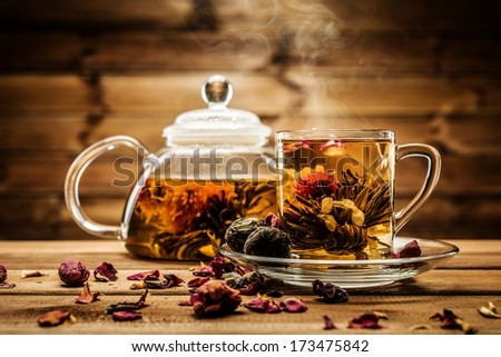 Teapot and glass cup with blooming tea flower inside against wooden background  - stock photo