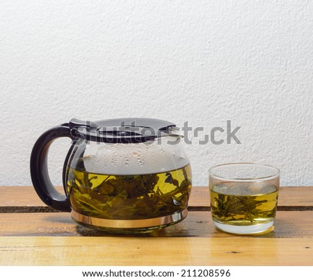 Teapot and glass cups with tea on wooden table at concrete wall background