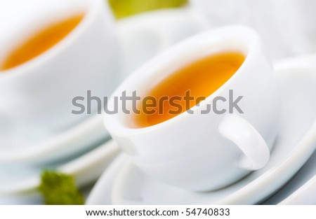 teapot and white teacup on white background - stock photo