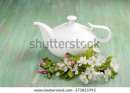 teapot white, apple blossom, cherry blossom, mint, on turquoise background - stock photo
