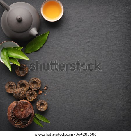 Teapot with cup and dry green tea pu-erh on black slate background, top view - stock photo