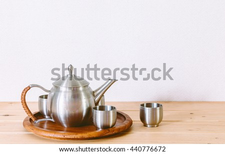 Teapot with cup of tea on wooden table