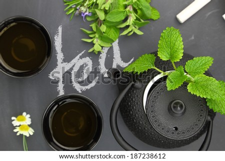 Teapot with herbs and teacups on chalkboard top shot - stock photo