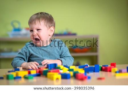 Tearful boy in nursery with Montessori toys - stock photo
