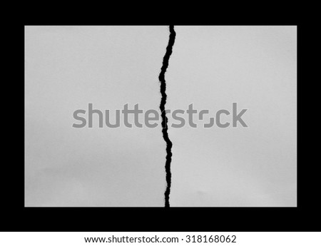tearing paper into two pieces on black - stock photo