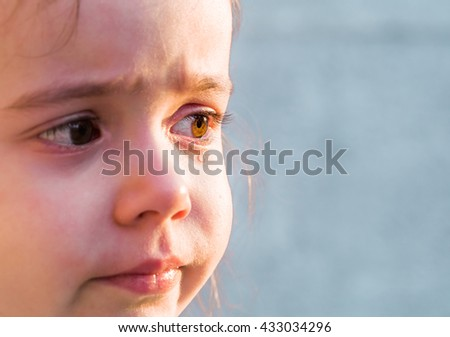 tears the emotions of a little girl, on the grey grass, the evening - stock photo