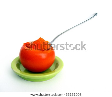 Teaspoon in ripe persimmon - stock photo