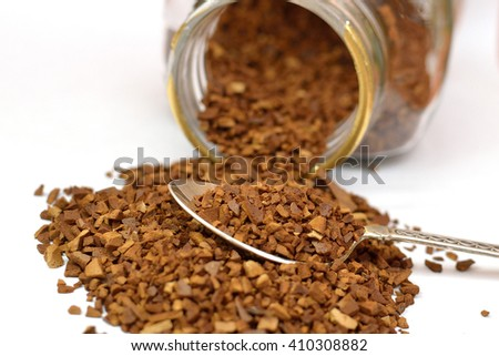 Teaspoon of instant coffee with some granules spilled around the spoon, isolated on a white background - stock photo