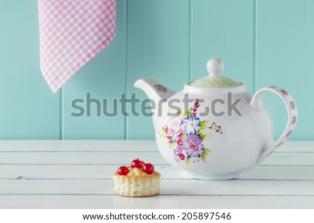 Teatime: a teapot and a vol-au-vent with red currants on a white wooden table with a robin egg blue background. Vintage Style. - stock photo