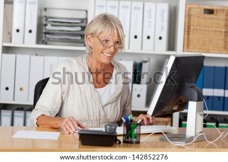 Tech savvy elderly woman working on the computer and smiling, sitting inside her office. - stock photo