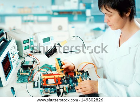 Tech tests electronic equipment in service centre - stock photo