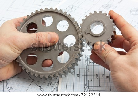 technical drawing and pinion gears in hands - stock photo