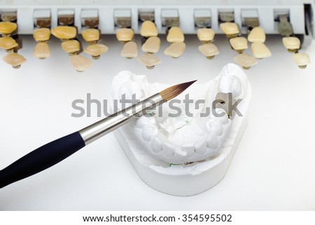 Technical shots of model on a dental prothetic laboratory  with accent in brush and ceramic tooth - stock photo