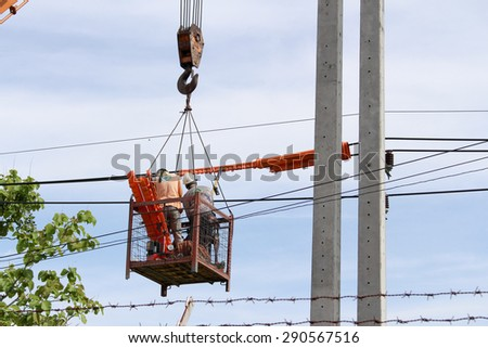 Technician connecting power cable on mobile crane - stock photo