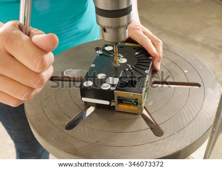 Technician destroying data on a hard drive by drilling through the platters with a Drill Press or a electric hand drill - stock photo
