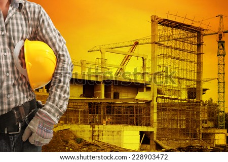 technician half body in protective safety equipment hard hat and tool belt  against building construction crane with beautiful sunset - stock photo