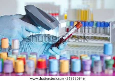 technician hands scanning barcodes on biological sample tube in the lab of blood bank / hands scanning a tube with barcode label for tracking blood sample - stock photo