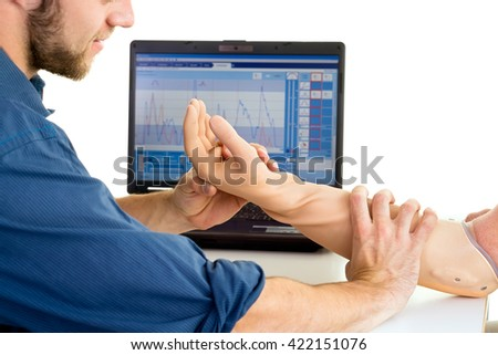 Technician helps man with prosthetic arm using computer against a white background