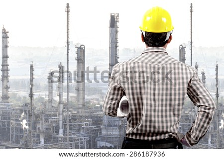 Technician holding blueprint for working at oil refinery petrochemical industrial plant