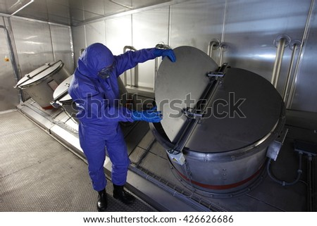 Technician in mask, blue uniform checking technological system n high tech environment - stock photo