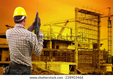 technician in protective safety equipment goggles hard hat with drill and tool belt  against building construction crane with beautiful sunset - stock photo