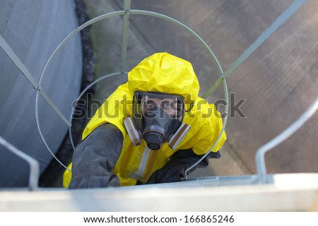 technician in protective uniform and mask  going up a metal ladder - stock photo