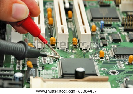 Technician in the service center testing electric circuit board - stock photo
