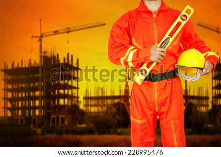 technician in uniform holding hard hat and yellow construction spirit level working at high building construction site against beautiful sunset - stock photo