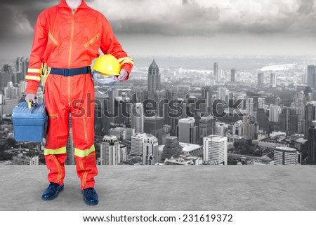 technician in uniform holding toolbox working at high building construction site against urban scene balcony over looking city dusky before rain falling  - stock photo