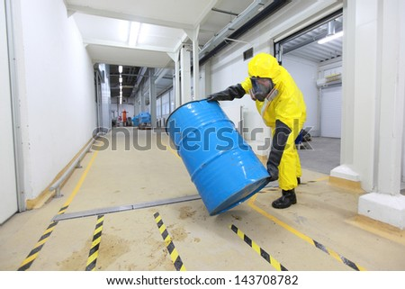 technician in uniform rolling barrel with hazardous substance - stock photo