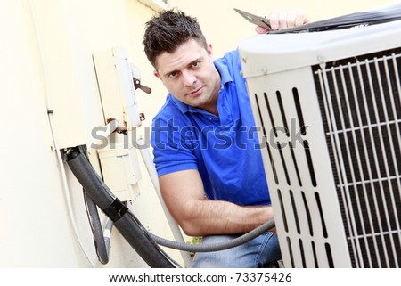 Technician inspects an AC unit - stock photo