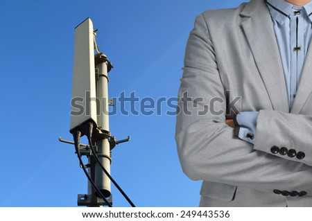 Technician Manager with Communication tower with micro cellular site under the blue sky. - stock photo