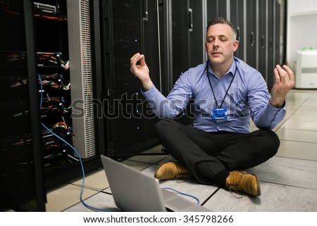 Technician meditating in server room at the data centre