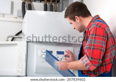 Technician servicing the gas boiler for hot water and heating - stock photo