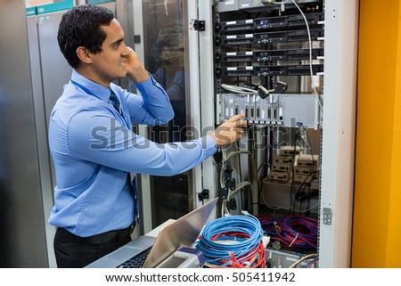 Technician talking on mobile phone while working in server room