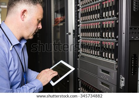 Technician using tablet pc while analysing server at the data centre