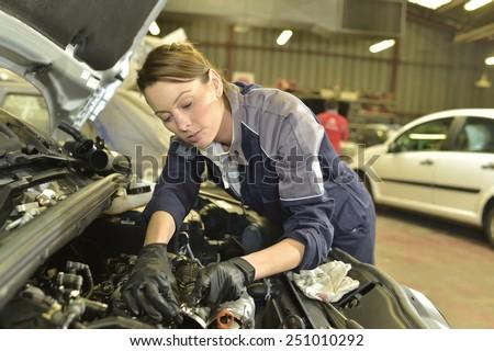 Technician woman working in auto repair workshop - stock photo