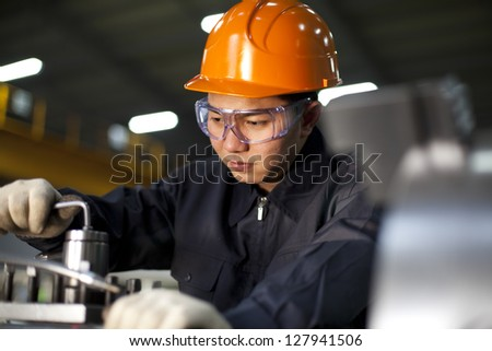 Technician working in factory shallow in focus - stock photo