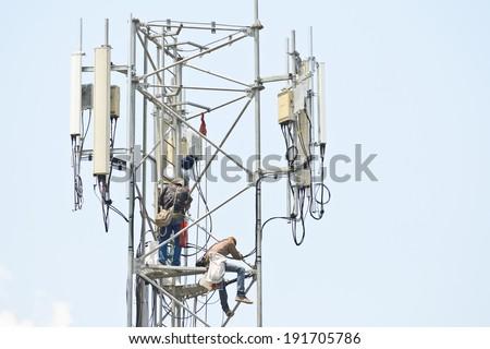 Technician working on communication towers - stock photo