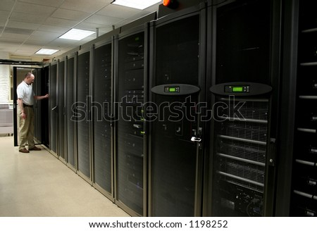 Technician working on racks of 1u and 2u servers in a computer room. - stock photo