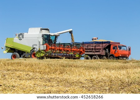 Technician works in the field for the harvest equipment for harvesting - stock photo